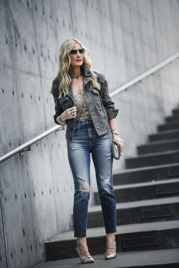 Blonde girl wearing army jacket and AG jeans