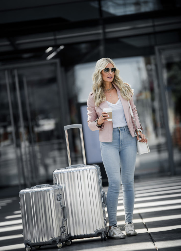 Dallas Blonde Traveling wearing faux leather jacket and Golden Goose Sneakers