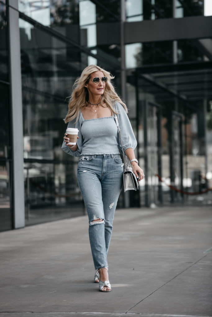 Dallas blonde wearing smocked top and Reformation mom jeans