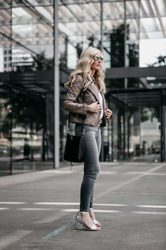 Dallas blonde wearing moto jacket and gray jeans