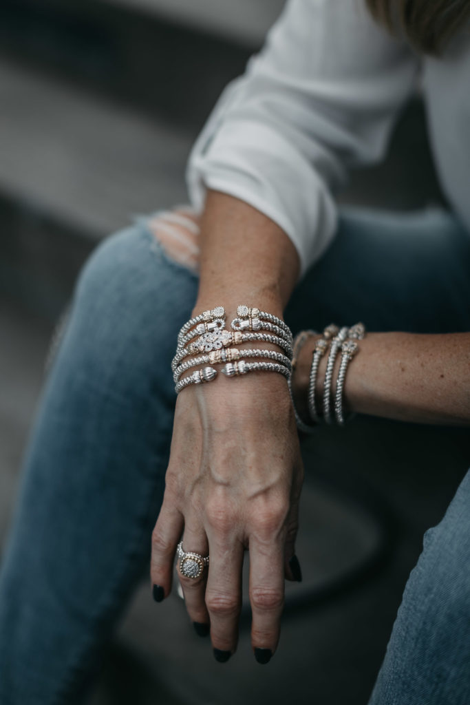Stacked bracelets and ripped denim