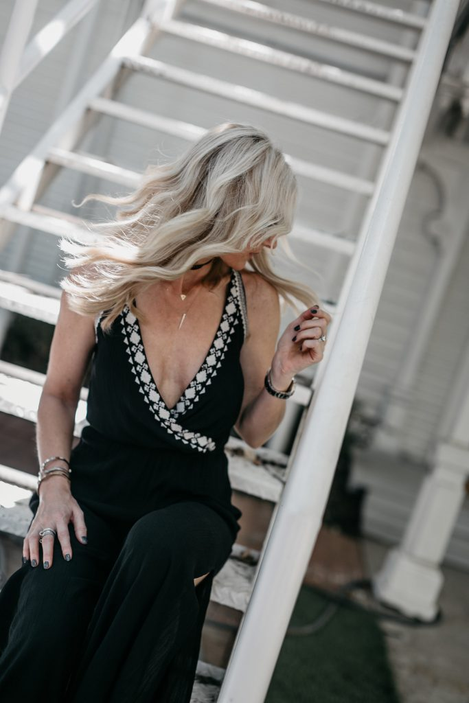 Dallas blonde woman wearing black jumpsuit