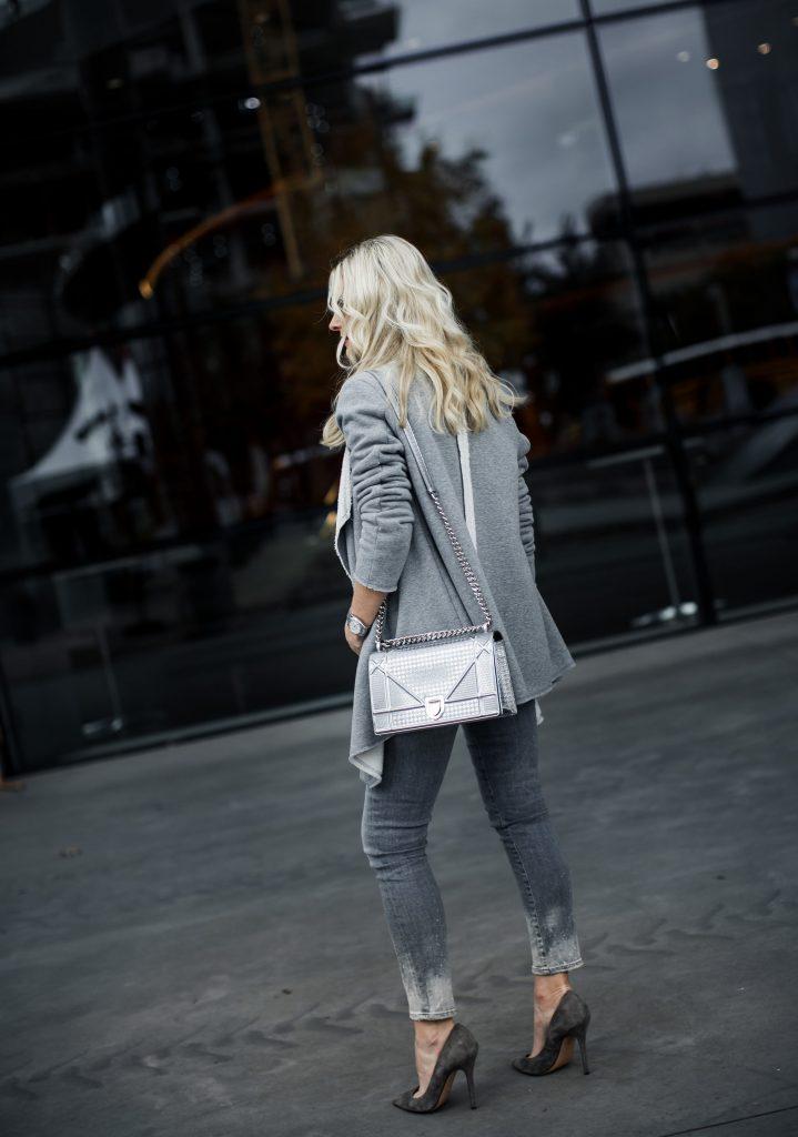 Silver Dior handbag and gray skinny jeans