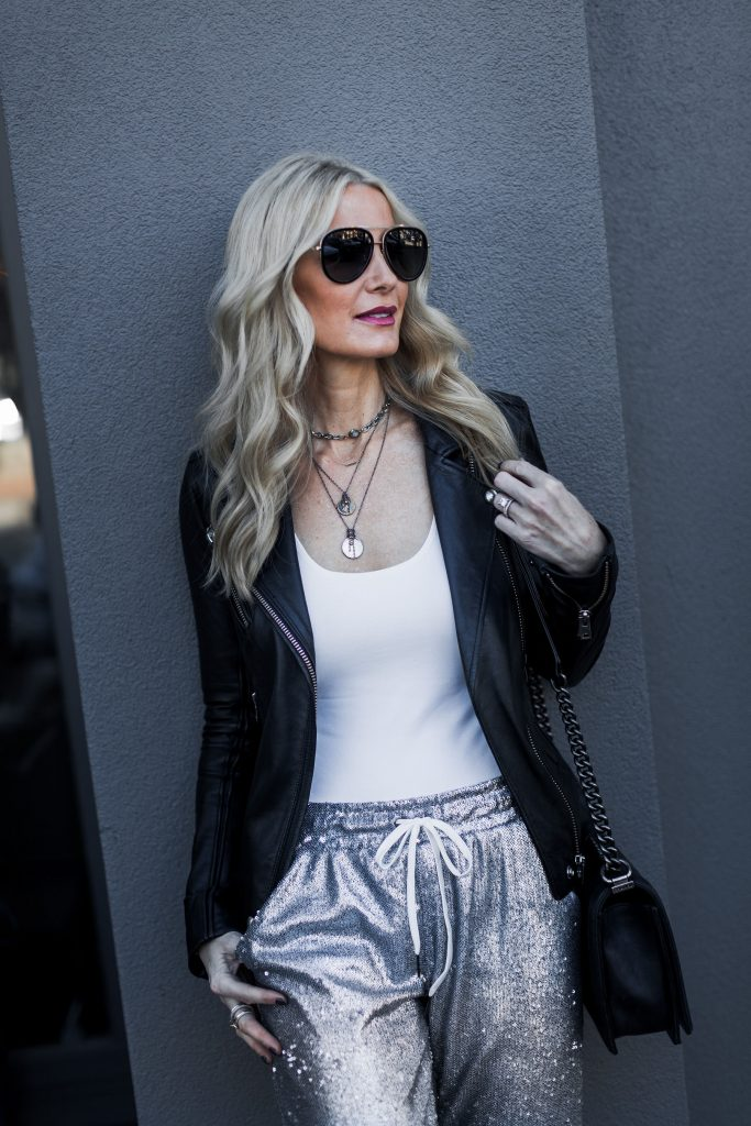 Dallas blonde woman wearing leather jacket and sequin joggers