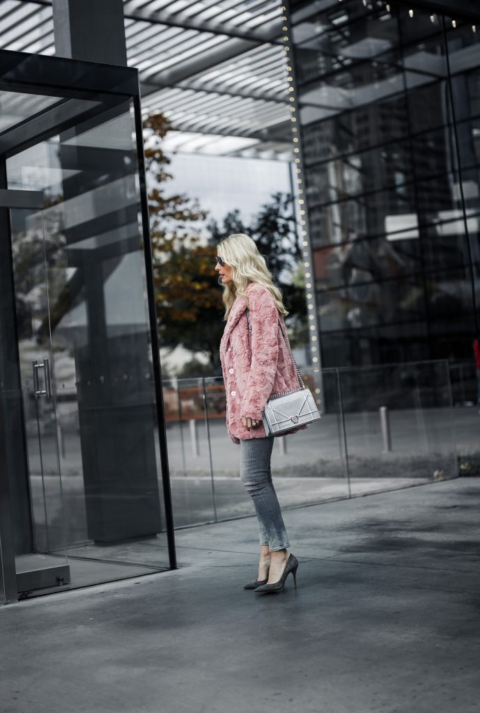 Dallas blogger wearing pink teddy coat and gray skinny jeans