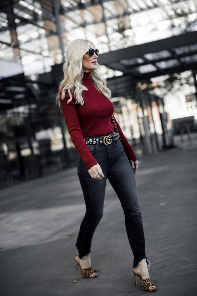 Dallas blonde woman wearing Gucci belt and red turtleneck sweater
