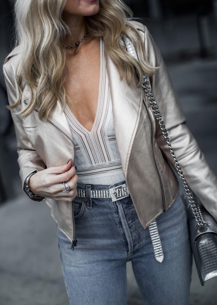 Metallic moto jacket, white bodysuit , Mom jeans, and Silver belt