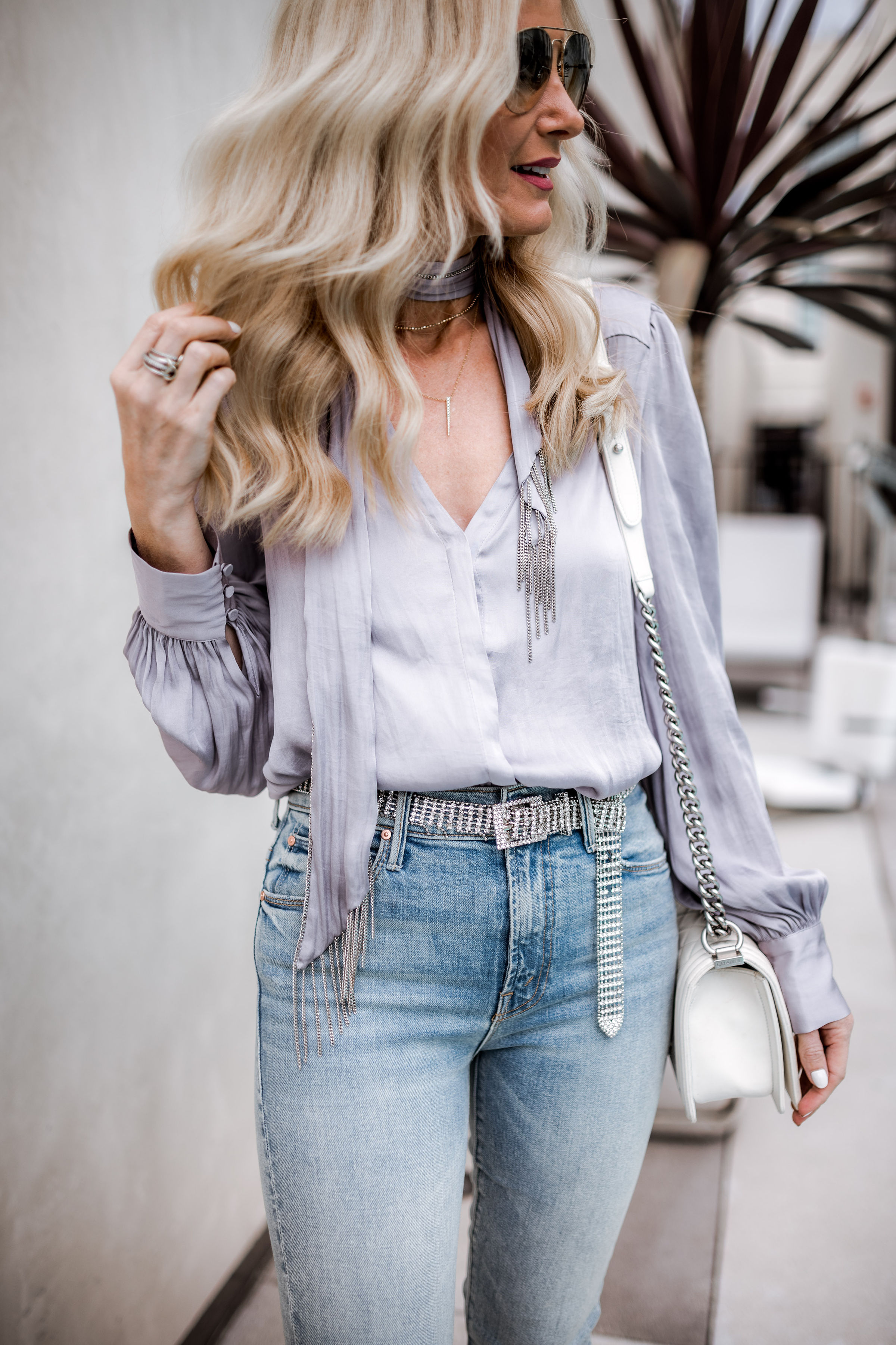 Dallas blonde woman wearing satin top and Mother denim skinny jeans