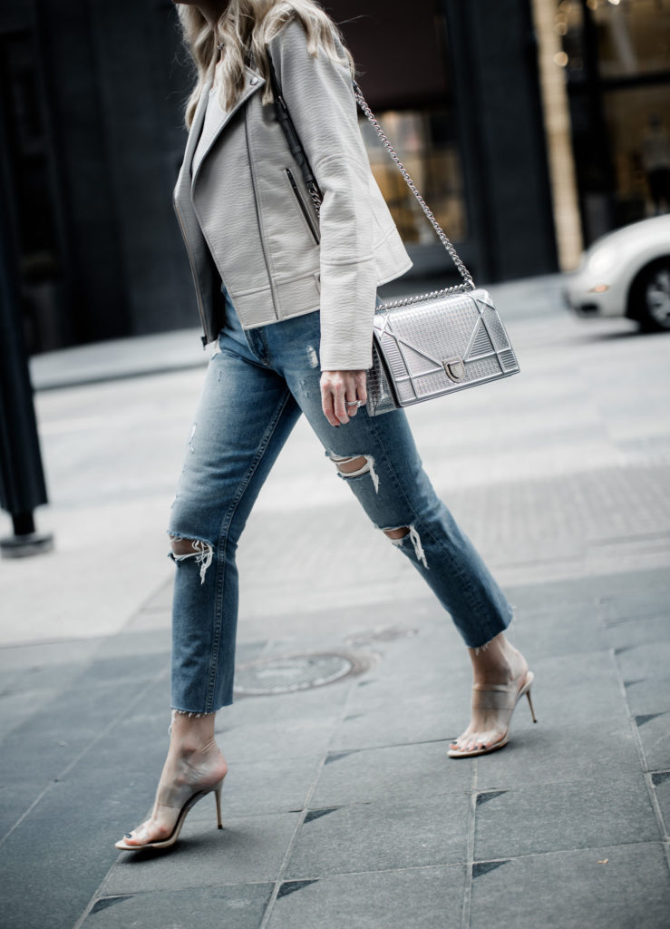 Dallas fashion blogger wearing ripped jeans, moto jacket, and heels