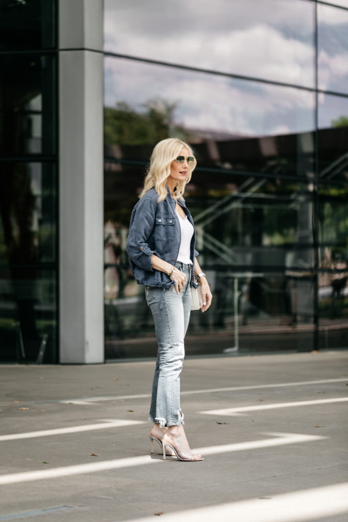 Dallas blonde woman wearing a blue field jacket and ripped jeans