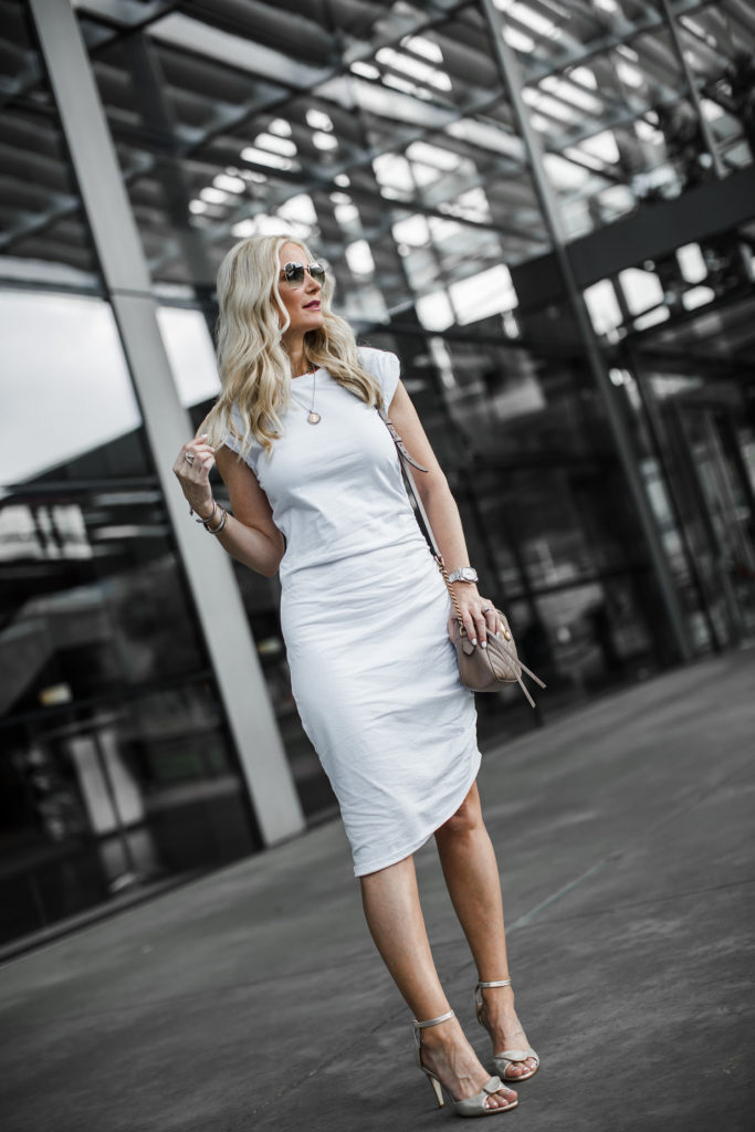 Dallas style blogger wearing a white dress and gold heels