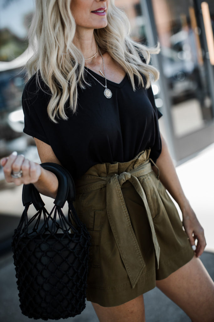 Dallas blogger carrying a black bucket bag by Staud