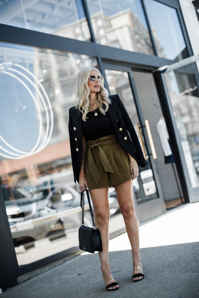Dallas influencer wearing a black Balmain blazer and paper bag waist shorts