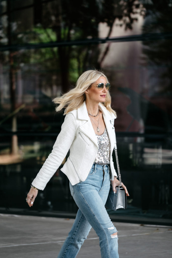 Dallas style influencer wearing a white moto jacket and ripped jeans