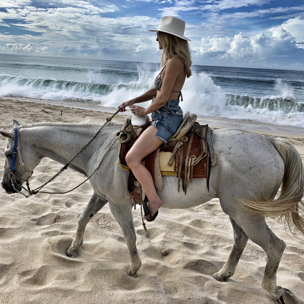 Dallas blogger riding a horse on the beach