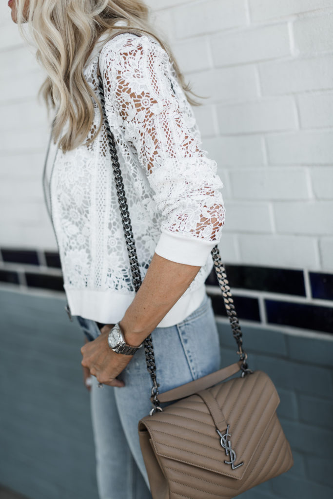 Dallas influencer wearing a white lace bomber jacket and carrying a YSL handbag
