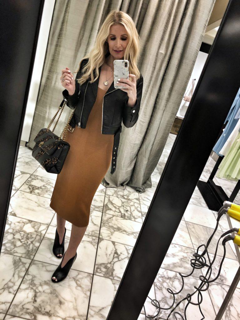 Dallas influencer wearing a midi dress and black moto jacket