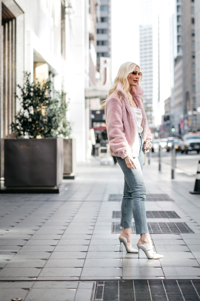 Style blogger wearing a blush colored jacket with denim and heels