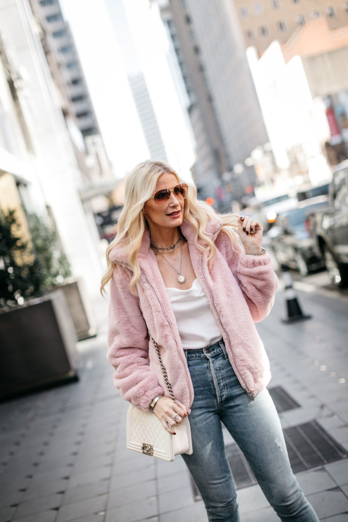 Fashion style blogger wearing a pastel faux fur jacket with denim