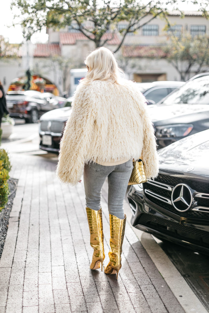 Dallas influencer wearing a faux fur jacket and gold boots