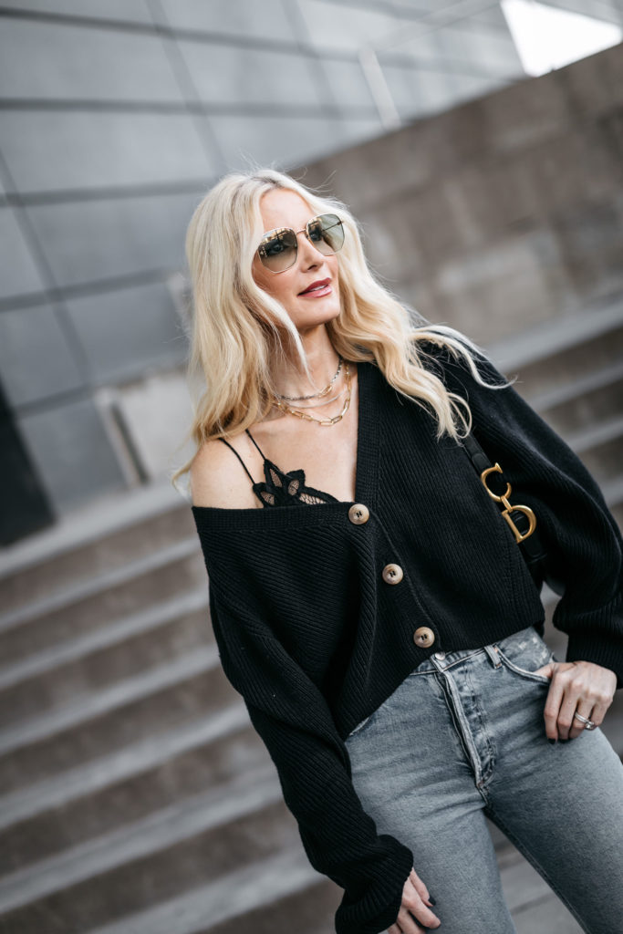 Fashion blogger wearing a black sweater with denim