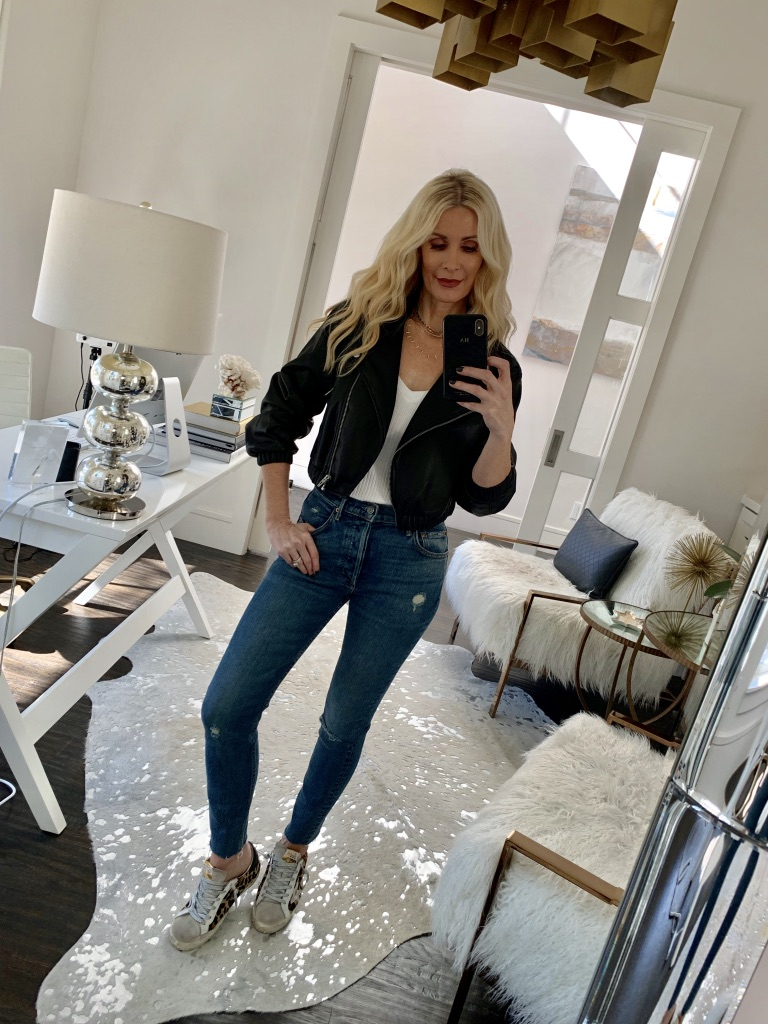 Dallas influencer wearing a black moto jacket and Golden Goose sneakers