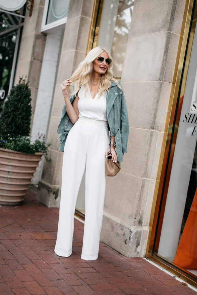Dallas influencer wearing a moto jacket and a white jumpsuit