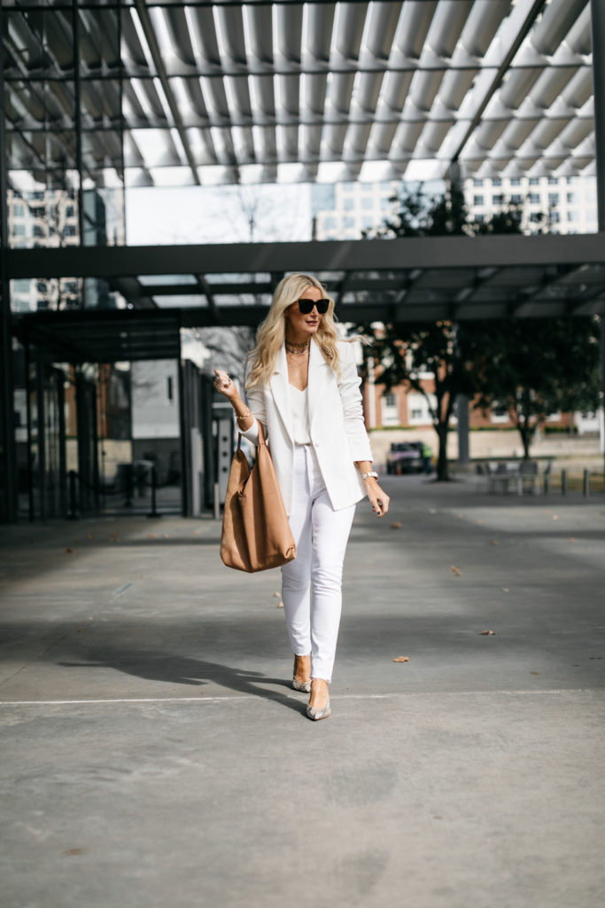 Style blogger wearing a white blazer and white jeans
