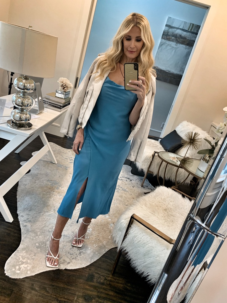 Dallas blogger wearing a blue midi dress and a white leather jacket
