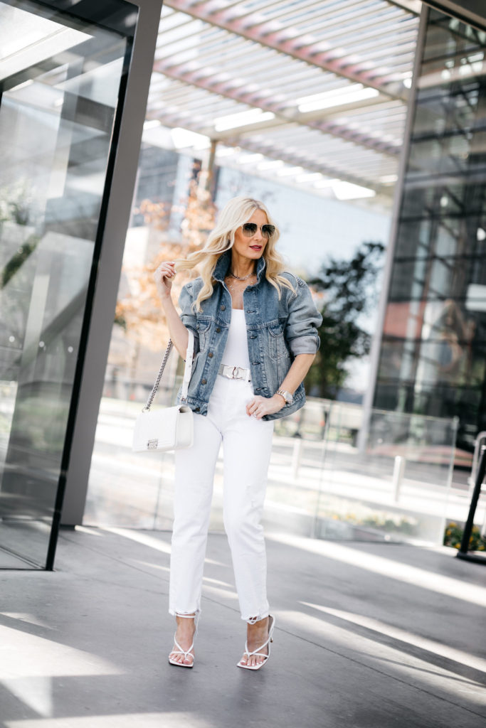 Fashion blogger wearing white jeans and a denim jacket