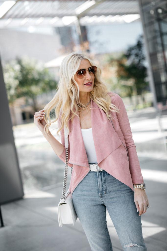 Dallas woman wearing a blush pink moto jacket