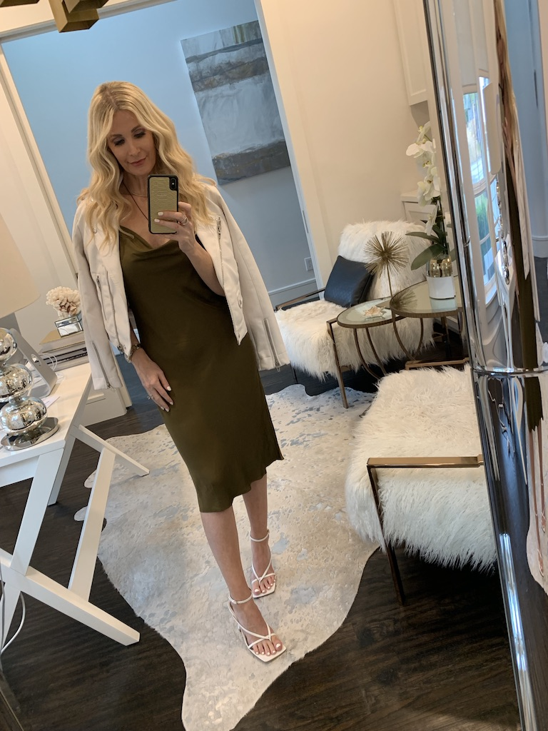 Style influencer wearing an olive green midi dress and white heels