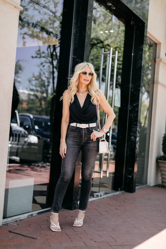 Fashion blogger wearing a black tank with black denim and white heels