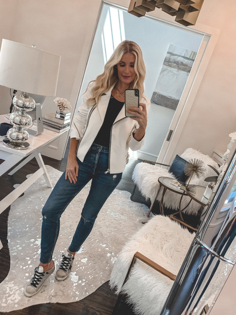 Style influencer wearing a white leather jacket and denim with sneakers
