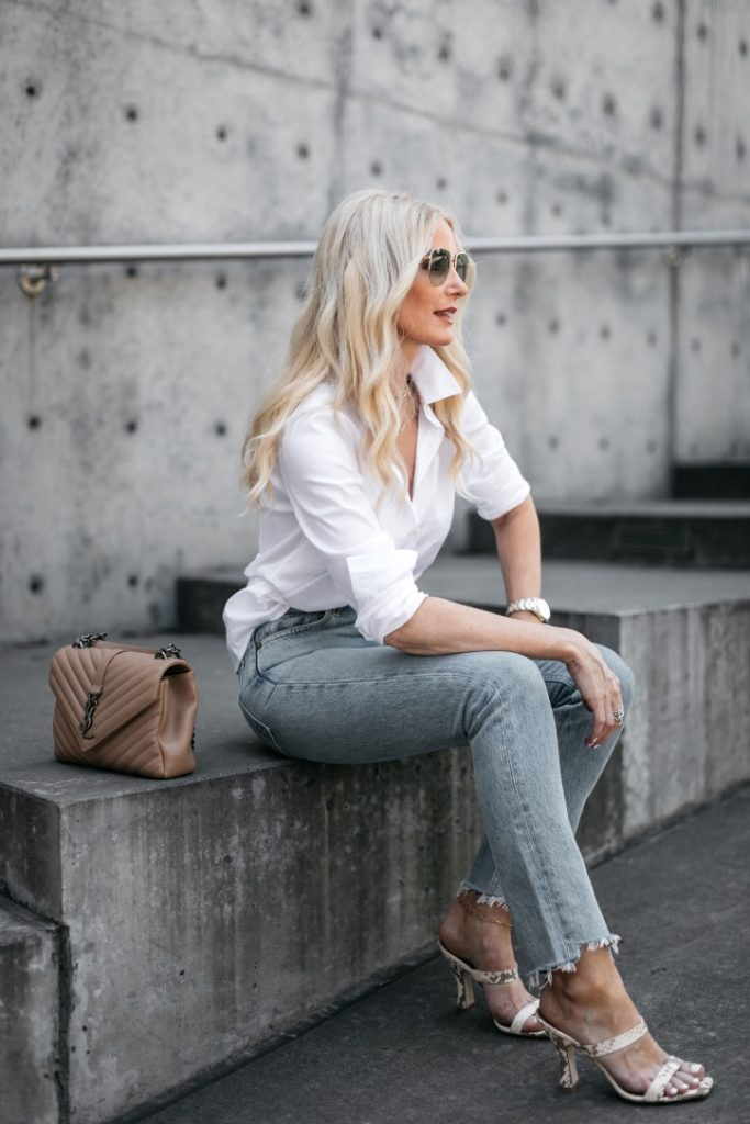 Style blogger wearing a white button down blouse and denim