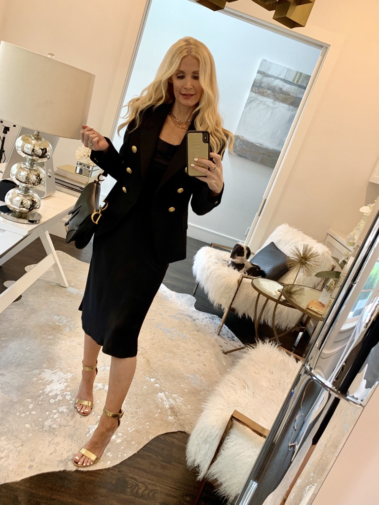Style blogger wearing a black jacket with gold buttons and a black slip dress