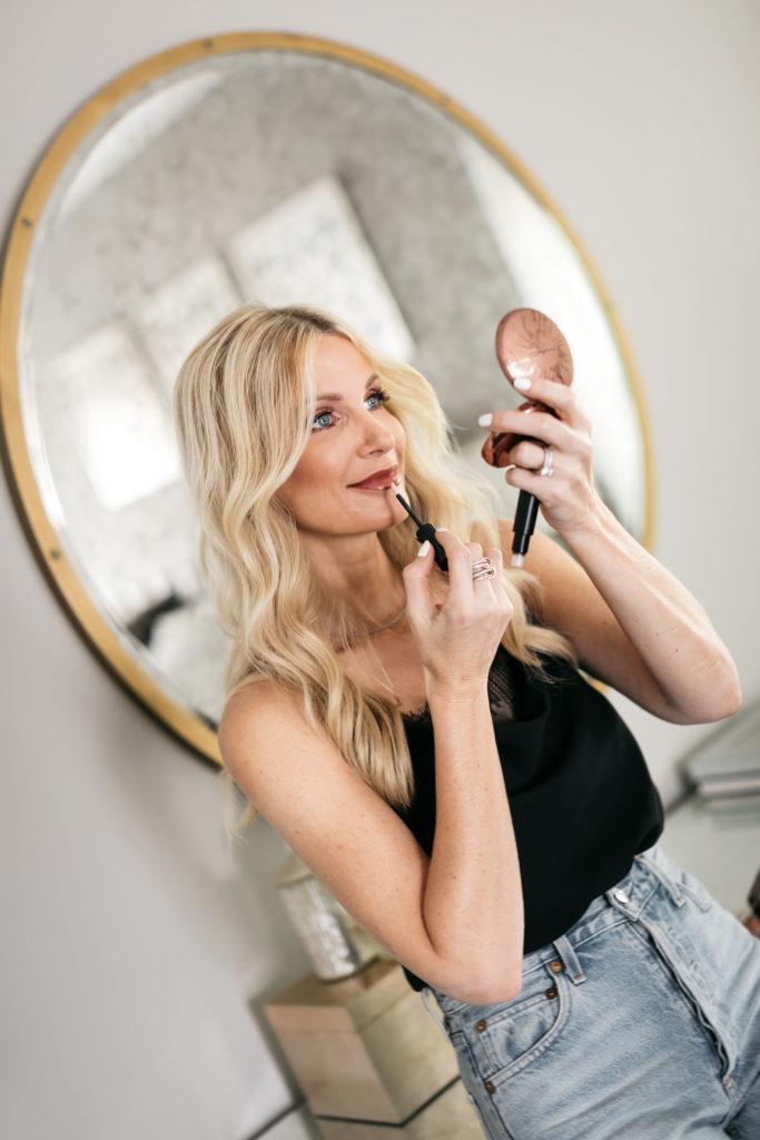 Dallas fashion blogger wearing a black cami and applying lip gloss