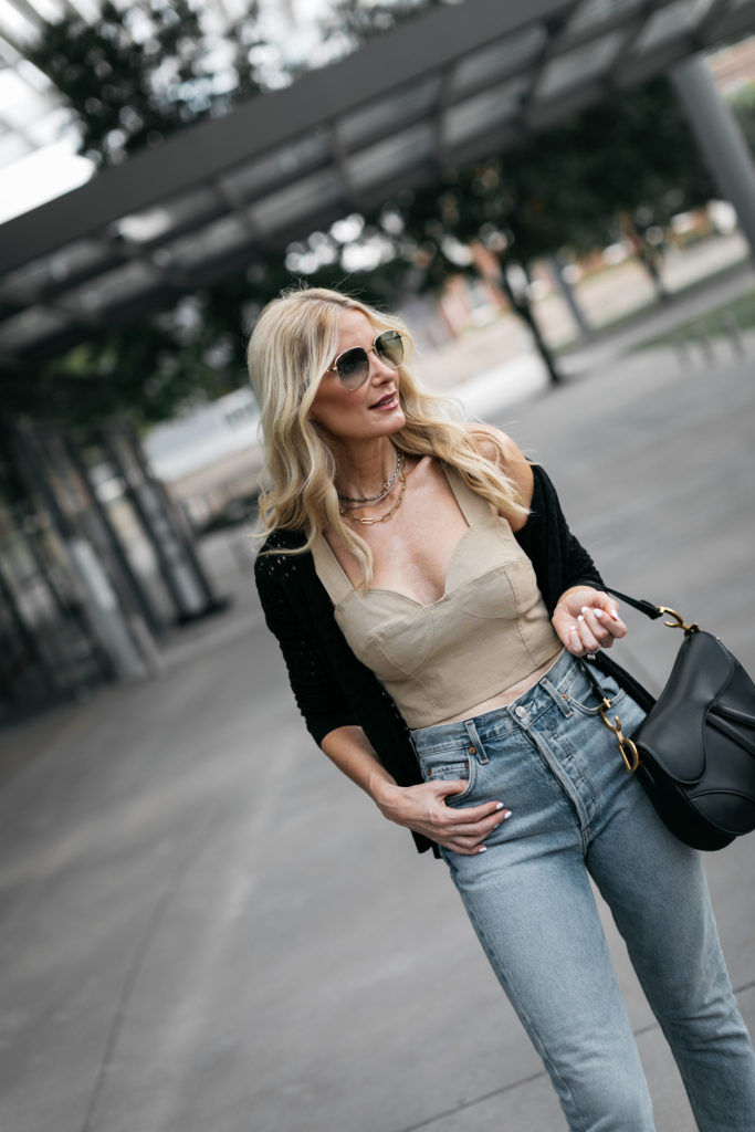 Style blogger wearing a neutral crop top with a black knit sweater