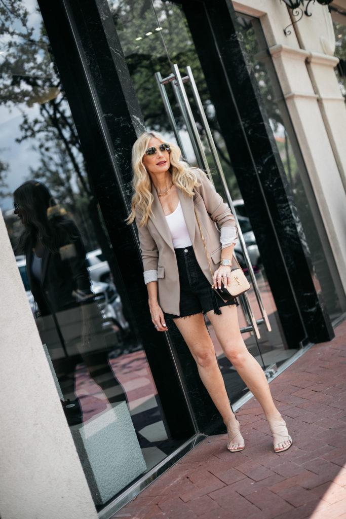 Dallas blogger wearing a neutral blazer and black denim shorts