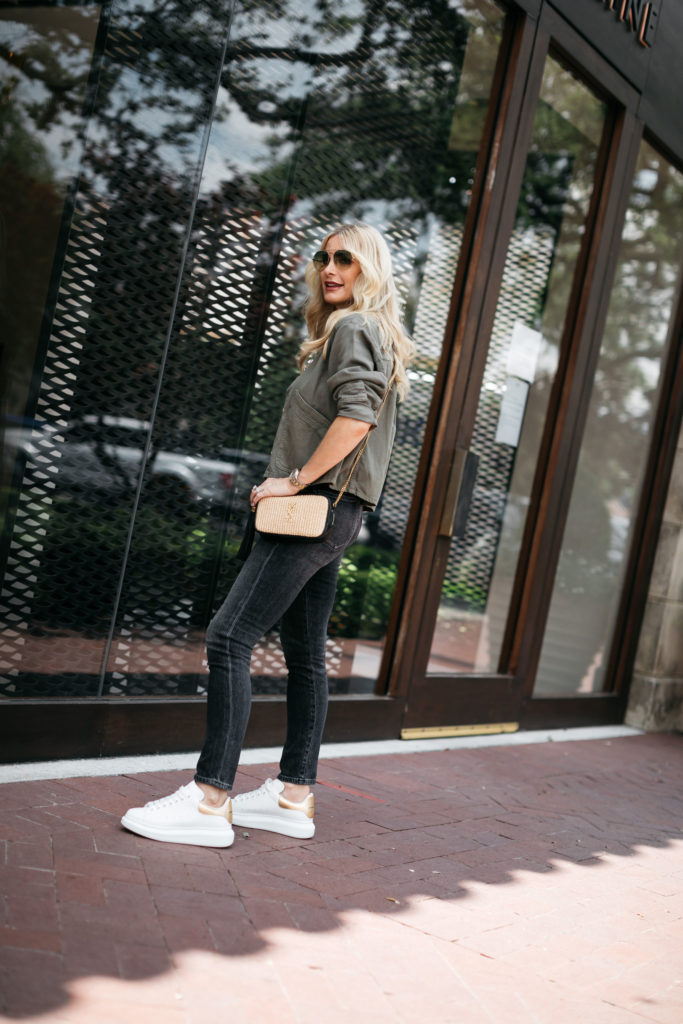 Dallas style blogger wearing black denim and white sneakers with an army green utility jacket