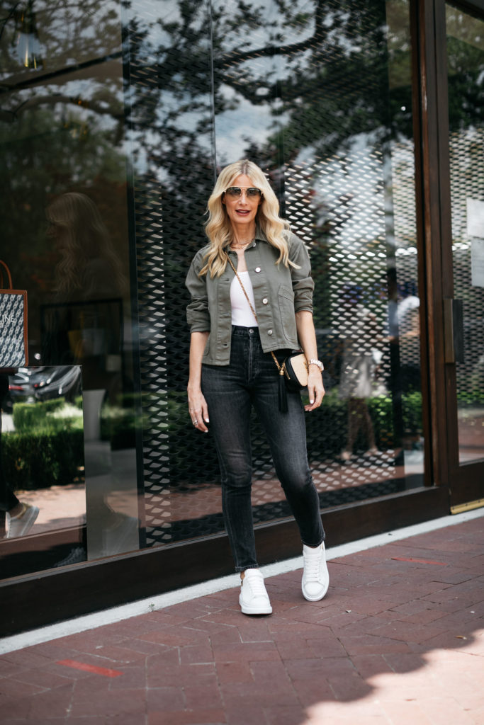 Style blogger wearing a white tank and utility jacket with black jeans