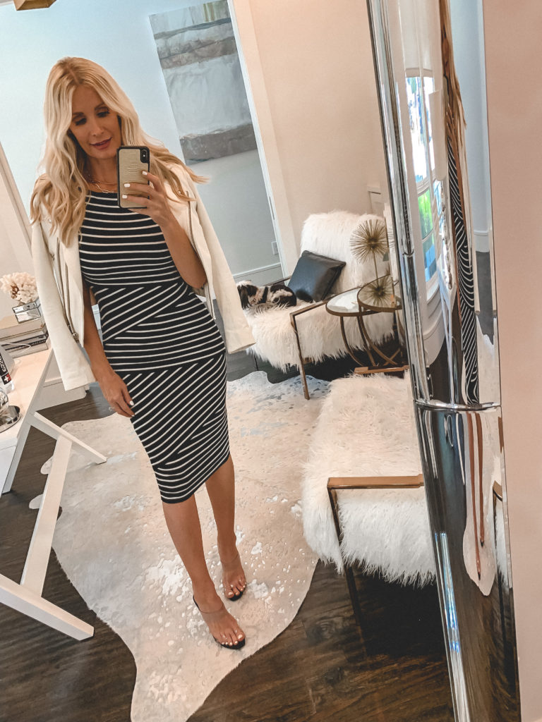 Dallas style influencer wearing a black and white striped midi dress and a white leather jacket
