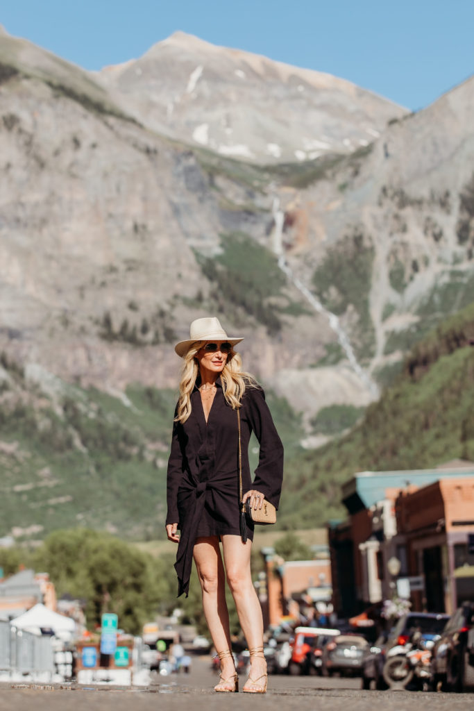 Blogger in the mountains wearing a black summer sundress and gold sandals