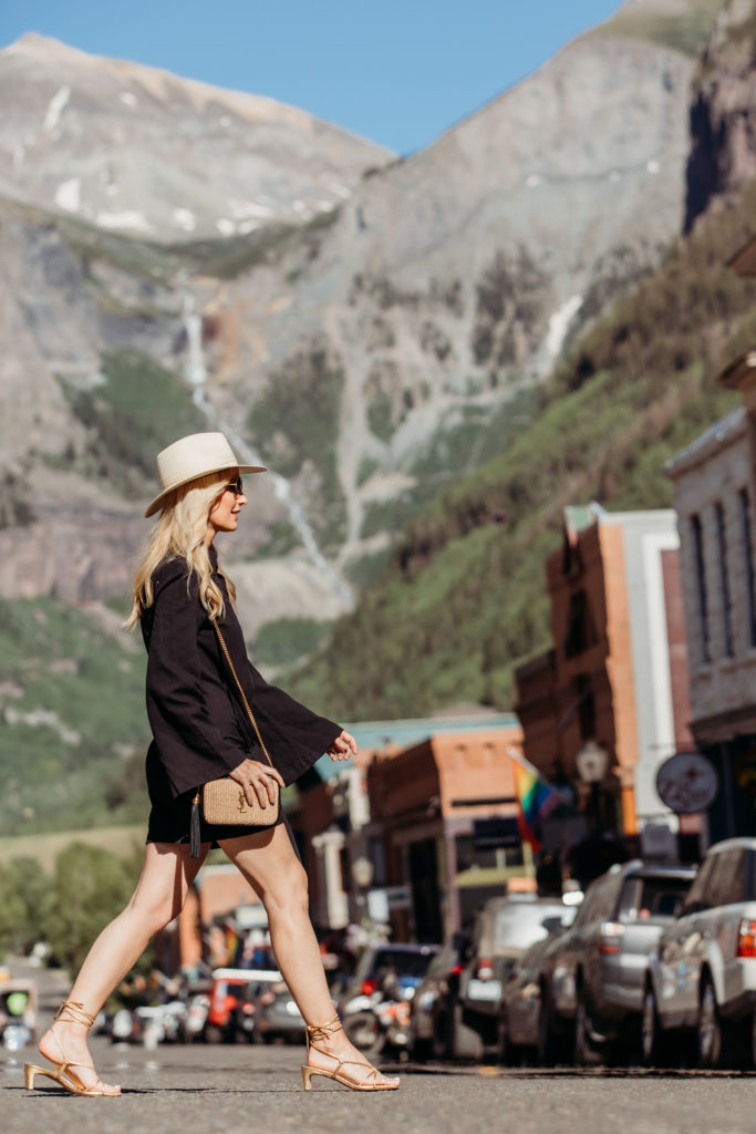 Fashion blogger in Telluride wearing a summer black dress and gold sandals