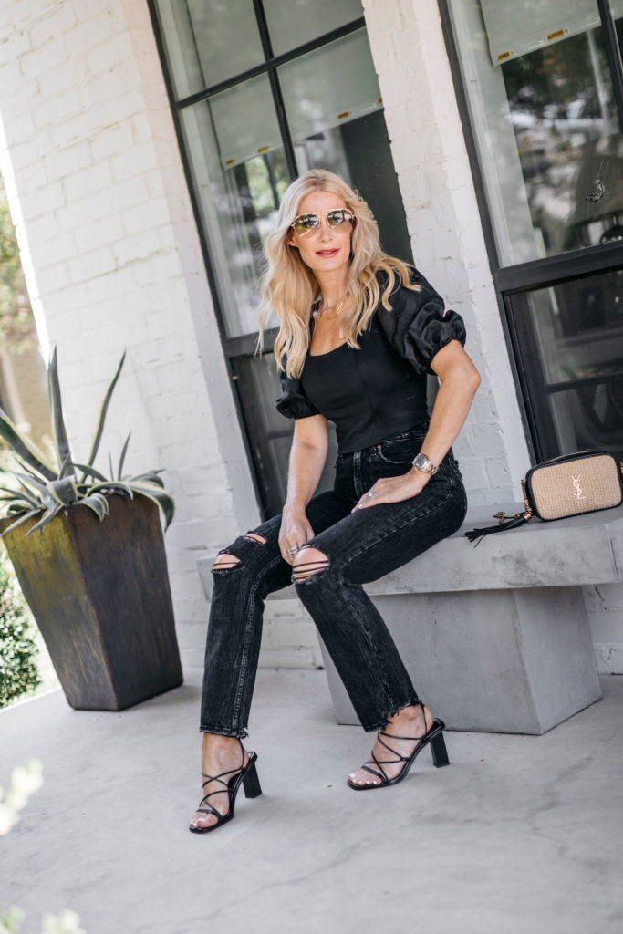 Dallas style blogger wearing ripped black denim and a black puff-sleeve top