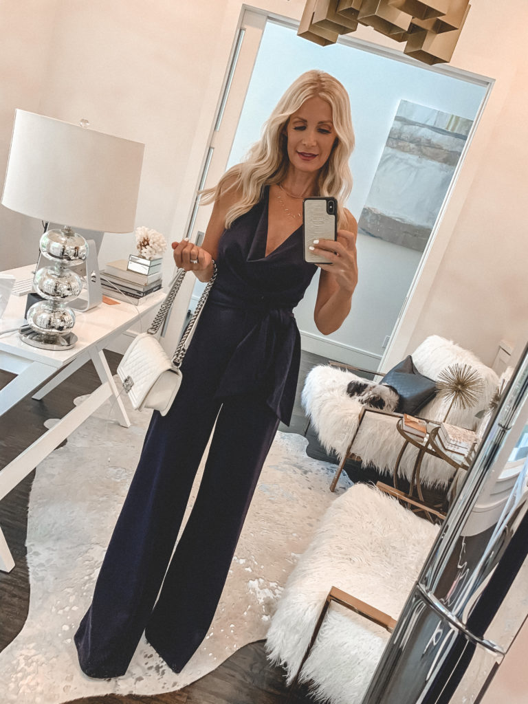 Dallas blogger wearing a navy jumpsuit and carrying a white handbag