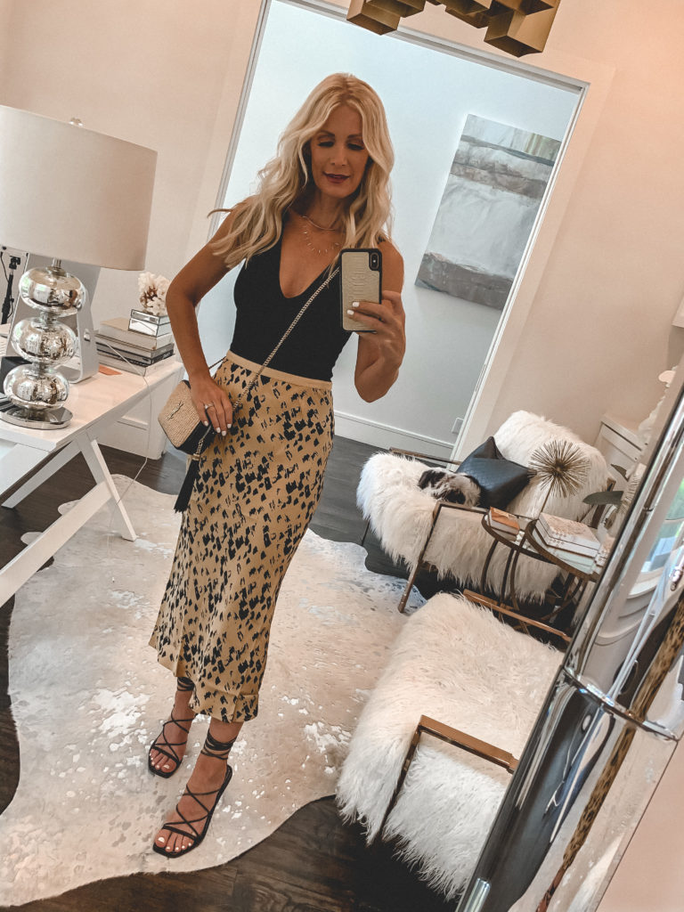 Fashion blogger wearing a leopard midi skirt and a black bodysuit