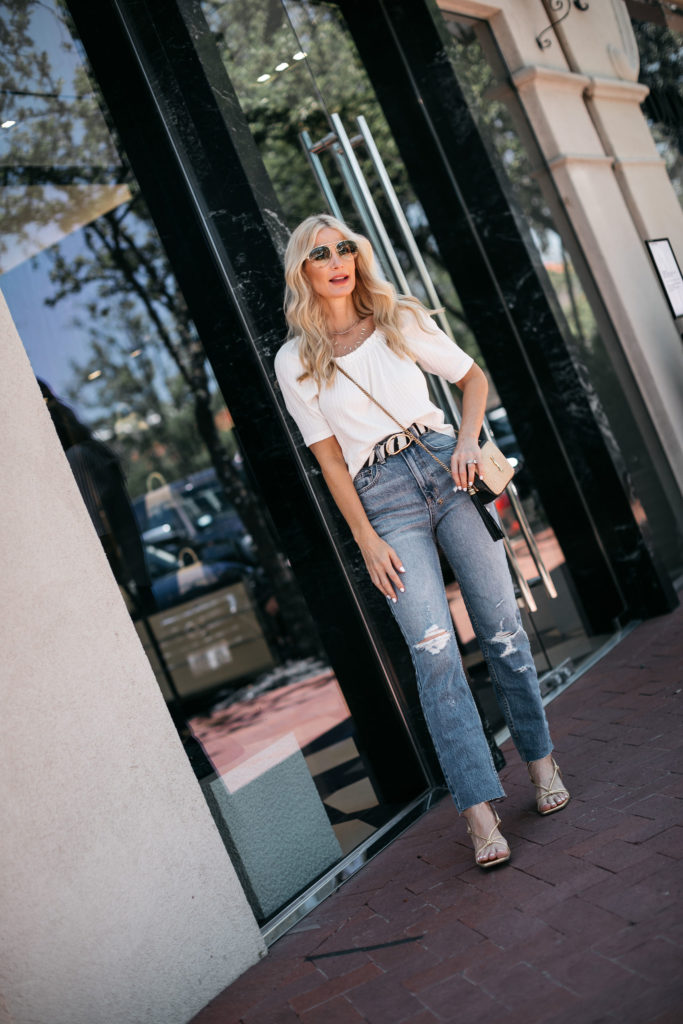 Fashion blogger wearing a white top with ripped denim and a zebra print belt