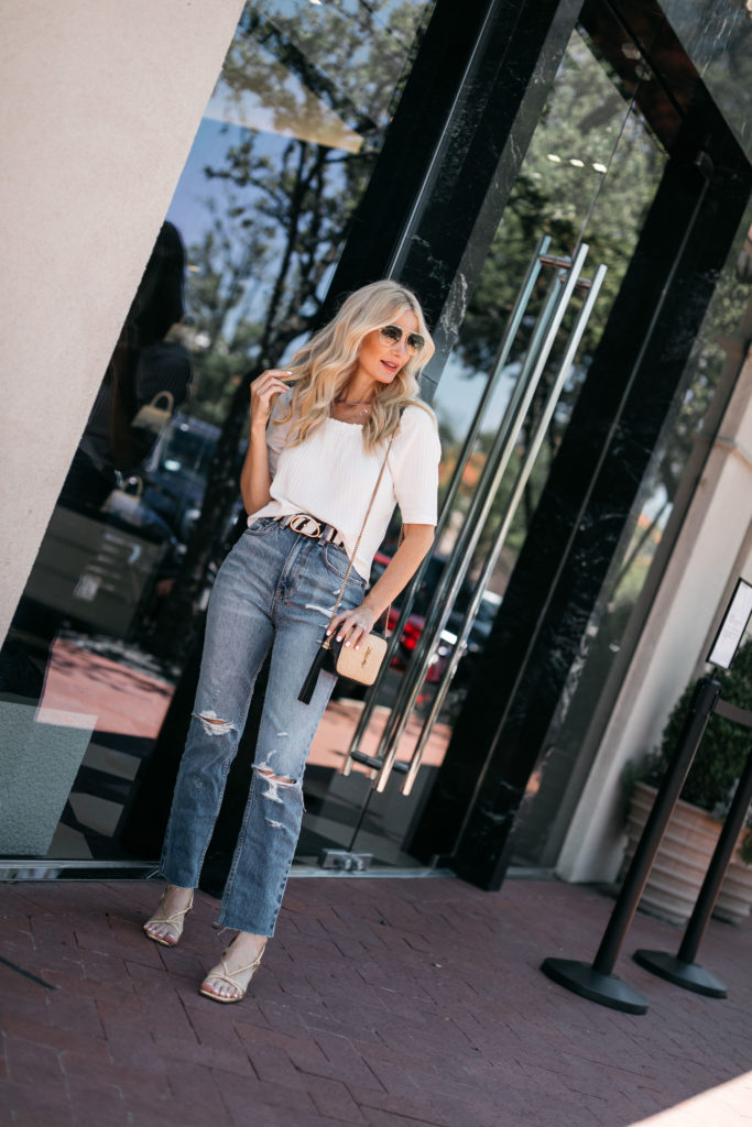 Style blogger wearing a white top and ripped denim