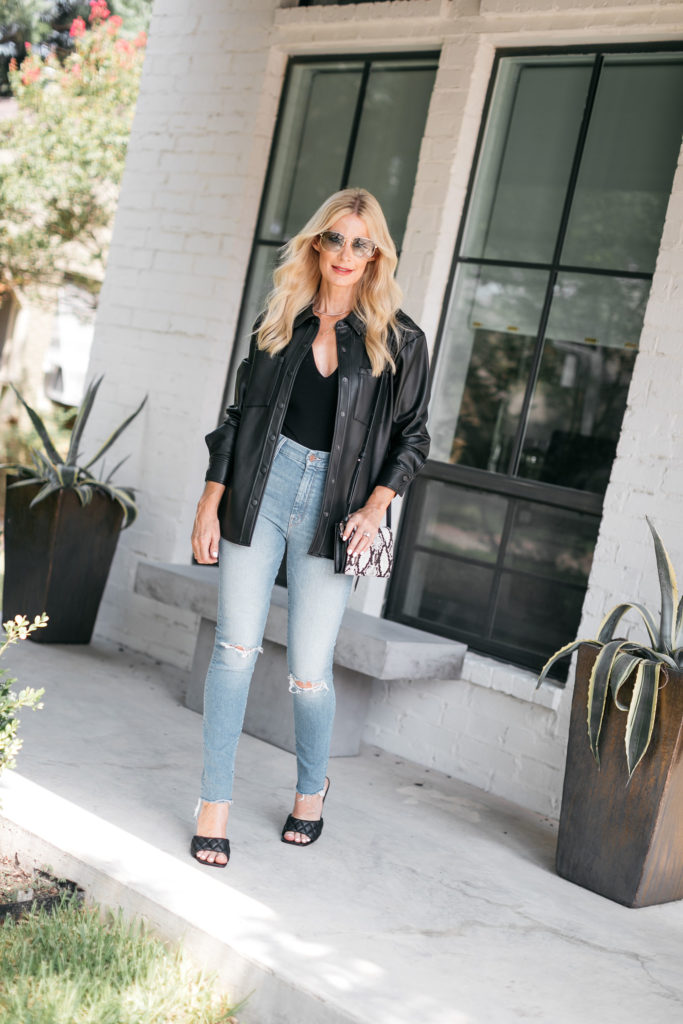 Dallas blogger wearing a faux leather shirt jacket and high waisted denim